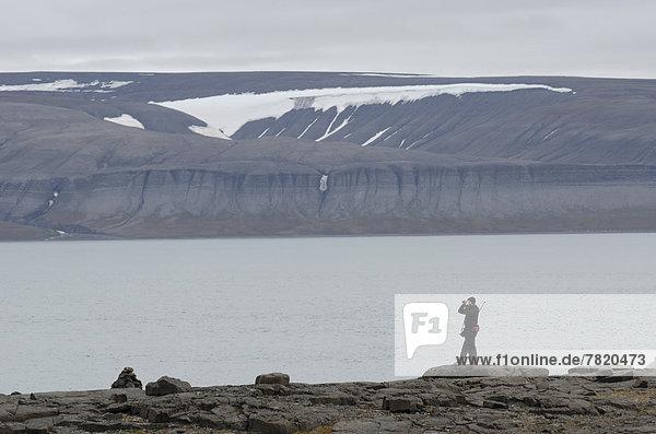 Person mit geschultertem Gewehr sucht Umgebung mit Fernglas nach Eisbären ab