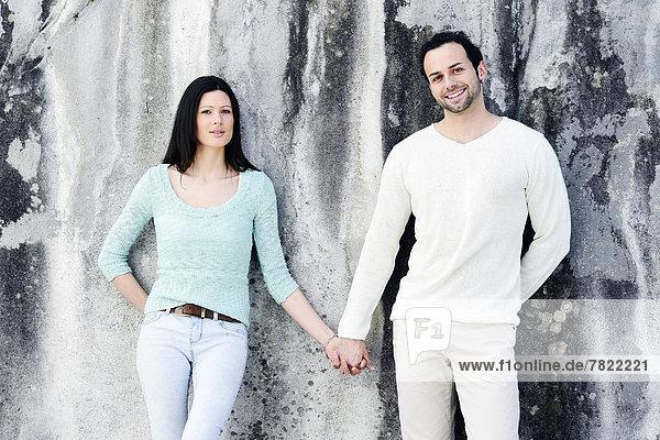 Junges Paar steht Hand in Hand an einer Wand Junges Paar steht Hand in Hand an einer Wand