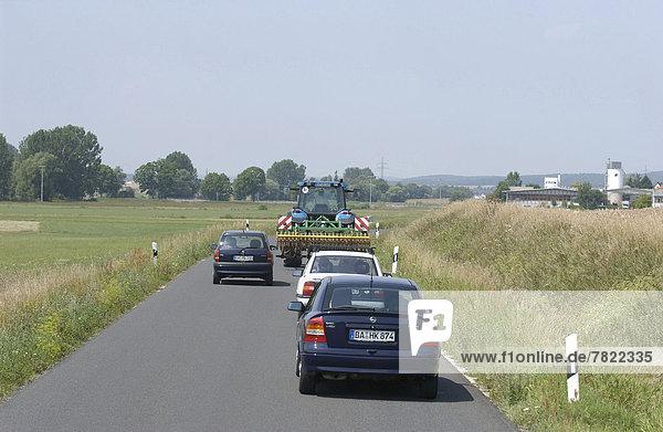 PKW überholt Traktor auf Landstraße