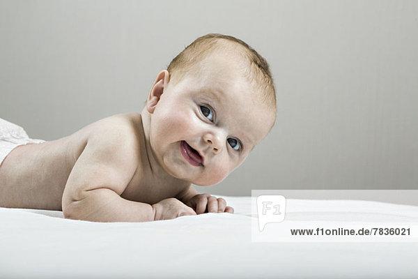 Studioaufnahme eines glücklichen Babys auf dem Bett liegend