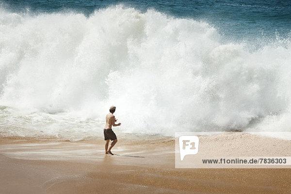 Mann vor großer Welle am Strand in La Graciosa  Kanarische Inseln  Spanien