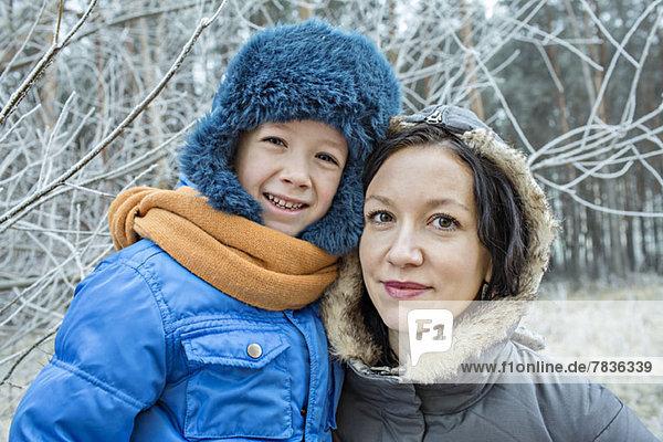 Eine fröhliche Mutter und Sohn in warmer Kleidung im Freien im Winter