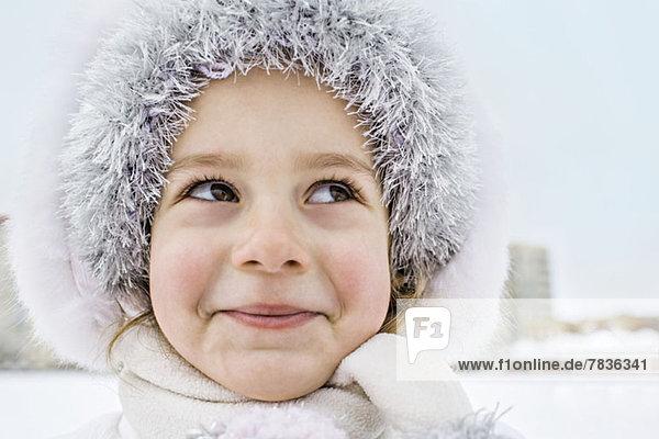 Ein schelmisch lächelndes junges Mädchen,  das im Winter draußen einen Pelzhut trägt