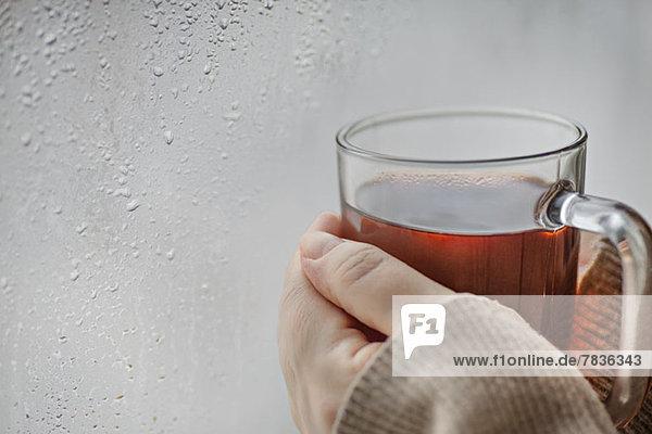 Menschliche Hände halten einen Becher Tee neben einem Fenster mit Kondenswasser.