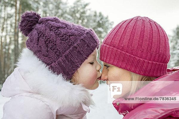 Eine Mutter und Tochter in warmer Kleidung,  im Freien,  von Angesicht zu Angesicht.