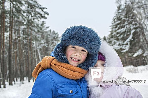 Ein fröhliches Geschwisterpaar in warmer Winterkleidung im Freien im Winter