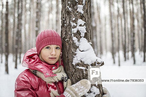 Eine Frau in warmer Kleidung,  die im Winter neben einem Baum posiert.