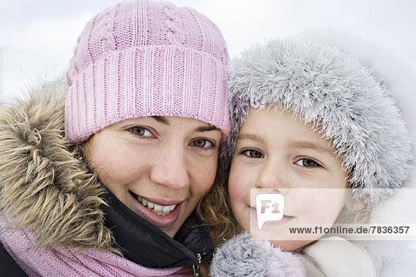 Eine fröhliche Mutter und Tochter in warmer Kleidung im Freien im Winter