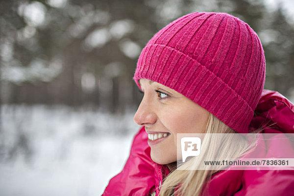Eine Frau in leuchtend rosa Winterkleidung im Freien