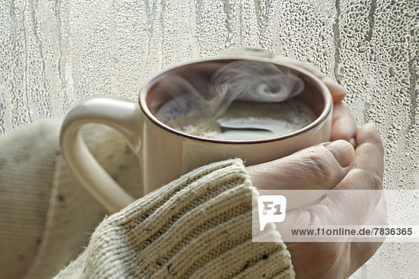Menschliche Hände halten eine Tasse mit aufsteigendem Dampf,  neben einem Fenster mit Kondenswasser.