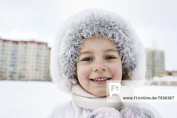 A cheerful young girl wearing warm clothing outdoors in winter