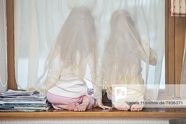 Schwestern auf der Fensterbank mit Blick aus dem Fenster