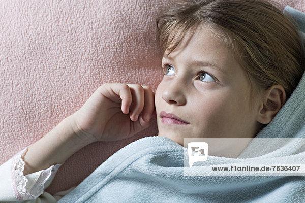 Tagträumendes Mädchen unter der Decke