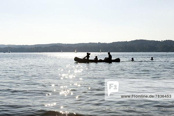 Drei Personen im Kanu vorbei an zwei Schwimmern am Starnberger Meer  Bayern  Deutschland
