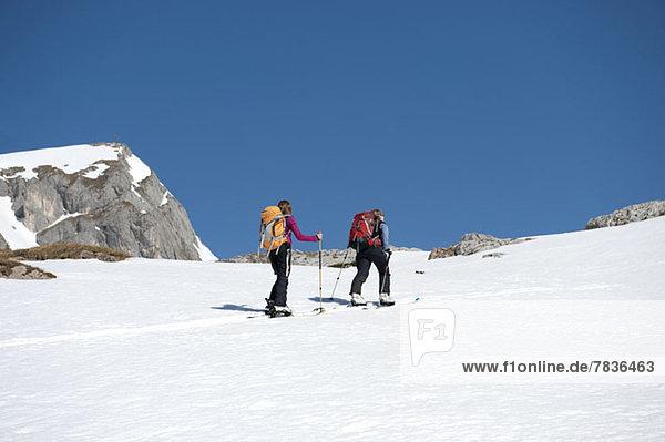 Zwei Skifahrer auf einer verschneiten Anhöhe in den Dolomiten  Südtirol  Italien