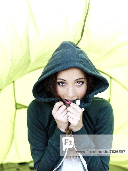 Ein Teenager-Mädchen sitzt in einem Zelt und zieht die Seiten ihres Kapuzen-Sweatshirts zusammen.