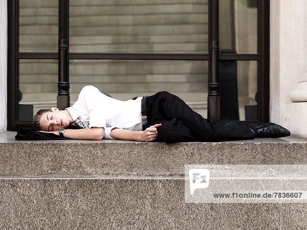 A young sleeping businessman lying on steps outside a building