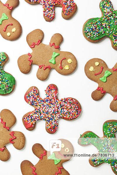 Diverse dekorierte Lebkuchenmänner-Kekse auf weißem Hintergrund