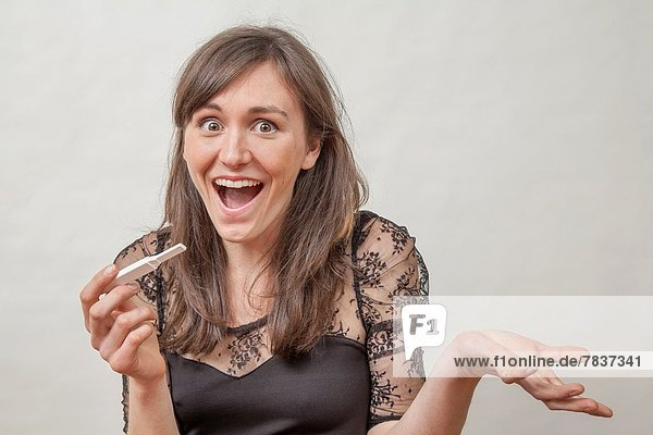 Young woman with a pregnancy tester.