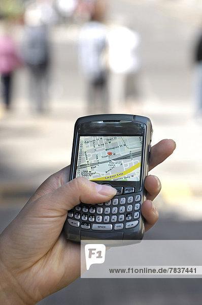 Hand hält ein BlackBerry 8310 Curve Smartphone  auf dem Display ein GPS-Stadtplan mit aktueller Position auf der Straße