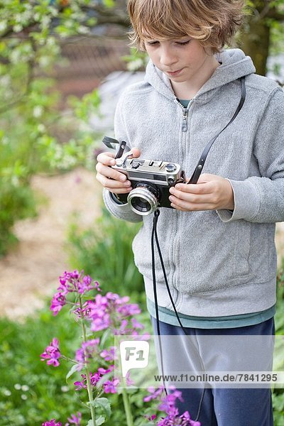 Boy photographing flowers in the garden.