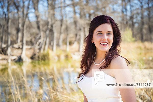 USA  Texas  Junge Braut im Brautkleid posiert am Frio River