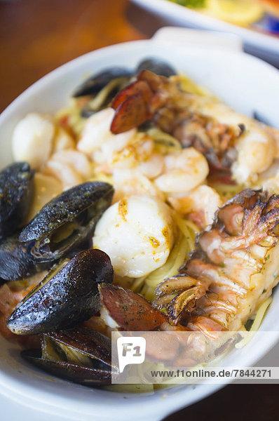 Meeresfrüchtegericht mit Hummer  Muscheln  Jakobsmuscheln und Nudeln auf dem Teller