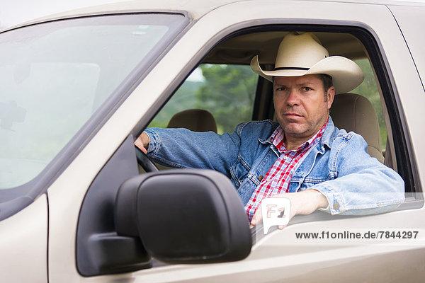 Texas  reifer Mann mit Cowboyhut im Pickup