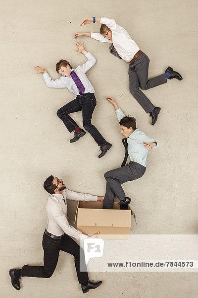 Geschäftsmann hält Pappschachtel  während Jungen ausfliegen