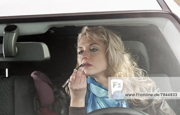 Frau  die Lippenstift im Auto anwendet
