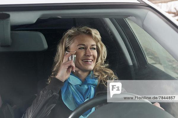 Frau spricht auf dem Handy im Auto
