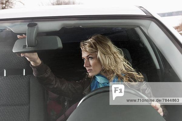 Frau schaut in den Rückspiegel