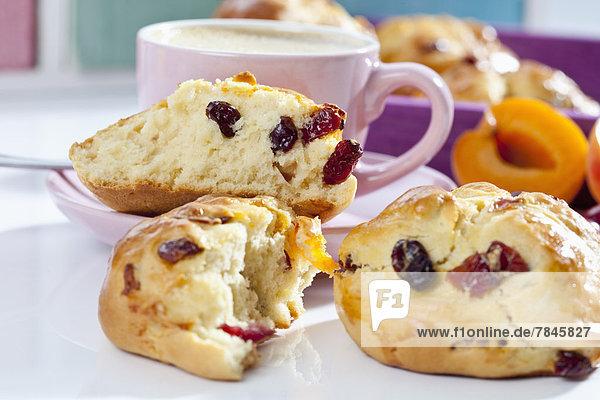 Cranberry Scones mit Aprikose und Tasse Kaffee auf weißem Hintergrund  Nahaufnahme