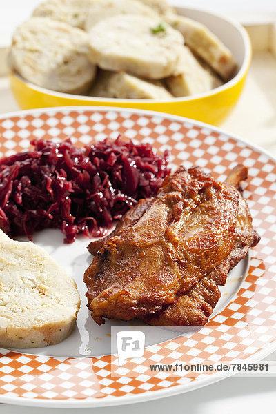 Schweinshaxe mit Semmelknödelscheiben und Rotkohl im Holztablett  Nahaufnahme