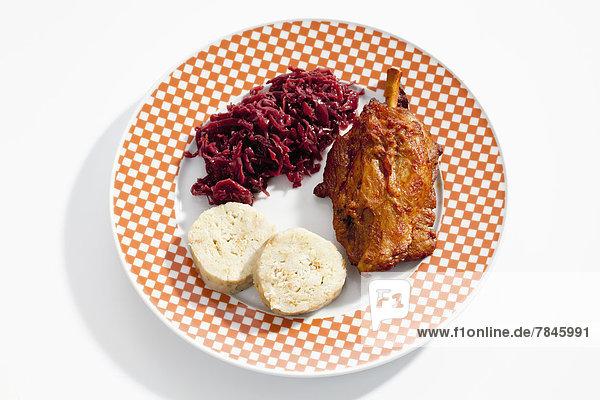 Schweinshaxe mit Semmelknödelscheiben und Rotkohl