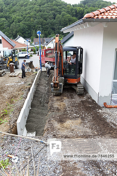 Europe  Germany  Rhineland Palatinate  Men installing corner stone in soil while house building