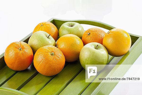 Green apples and oranges on wooden tray  close up