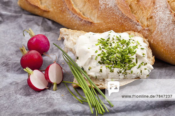 Bread with cream cheese  chives and red radishes on textile  close up
