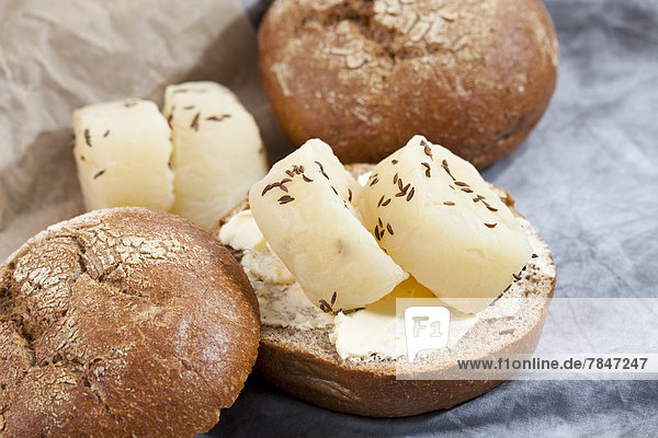 Rye roll with Harzer Roller cheese and caraway on textile  close up