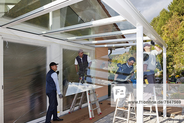 Germany  Rhineland Palatinate  Men assembling glass canopy