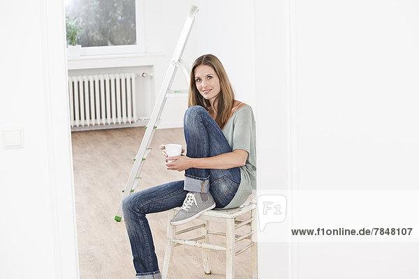 Porträt einer Frau mit Tasse auf einem Stuhl sitzend  lächelnd