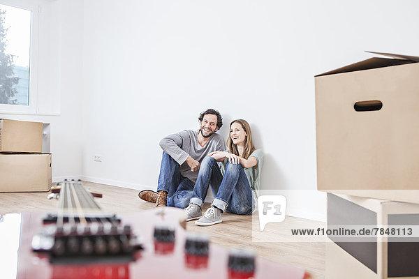 Paar auf dem Boden sitzend mit Umzugskartons  lächelnd