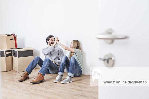 Paar sitzt auf dem Boden und gibt High Five  lächelt