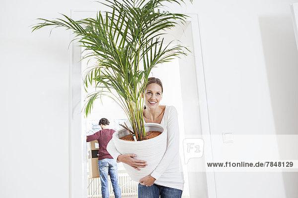 Frau beim Entladen der Topfpflanze  während der Mann im Hintergrund steht.