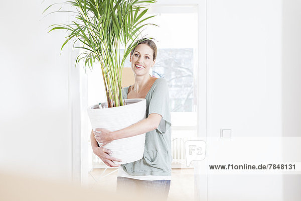 Frau hält Topfpflanze  lächelnd