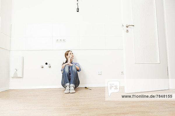 Frau auf dem Boden sitzend  wegschauend