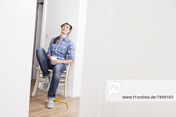 Frau sitzt auf Stuhl mit Tasse