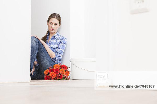 Frau sitzt auf dem Boden neben einem Blumenstrauß und einem Eimer.