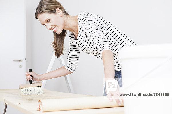 Frau beim Auftragen von Leim auf die Tapete