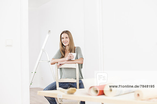 Frau sitzend auf Stuhl mit Tasse  Tapete auf Tisch im Vordergrund